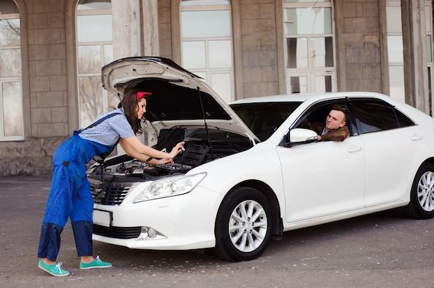 Śliczna atrakcyjna dziewczyna egzamininuje samochodowego silnika przy auto naprawy sho
