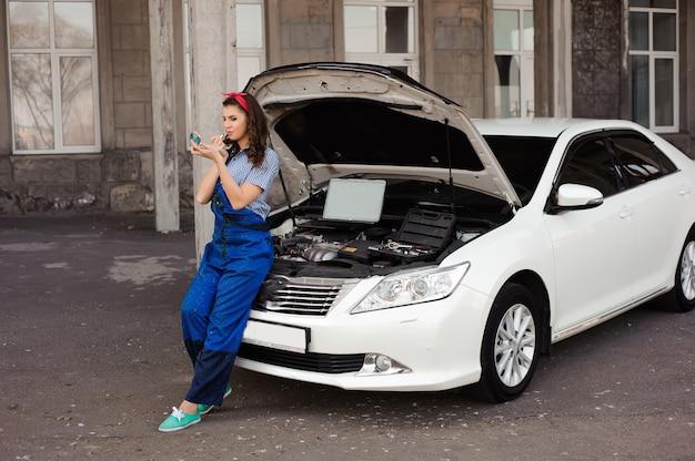 Śliczna atrakcyjna dziewczyna egzamininuje samochodowego silnika przy auto remontowym sklepem.