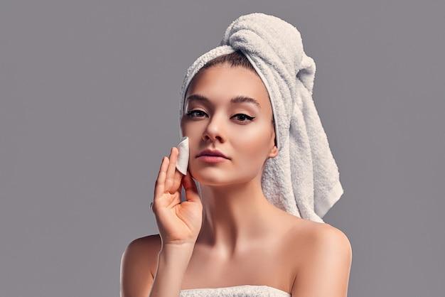 Śliczna atrakcyjna dziewczyna z ręcznikiem na głowie pociera twarz wacikiem z balsamem na białym tle na szarym tle. koncepcja pielęgnacji skóry.