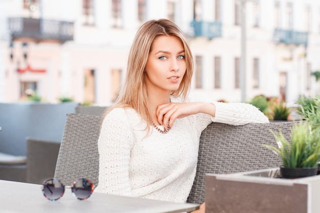 Śliczna atrakcyjna młoda kobieta o niebieskich oczach w stylowym swetrze z dzianiny siedzi na kanapie vintage w kawiarni na świeżym powietrzu. piękna dziewczyna odpoczywa.