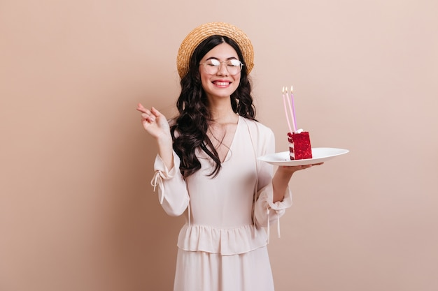 Śliczna azjatka śmiejąca się podczas życzenia urodzinowego. wyrafinowana japonka w kapeluszu, trzymając kawałek ciasta.
