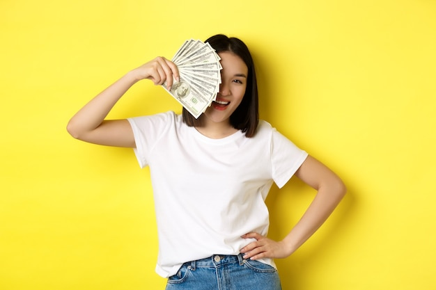 Śliczna azjatka ukrywa twarz za pieniędzmi, zerkając na aparat zadowolony, zarabia pieniądze, stojąc nad żółtym.