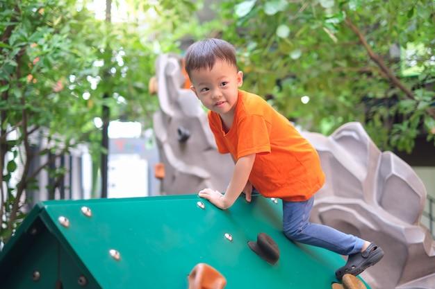Śliczna azjatycka berbeć chłopiec ma zabawę próbuje wspinać się na sztucznych głazach przy boiskiem na naturze