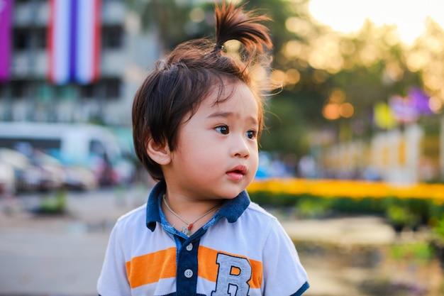 Śliczna azjatycka chłopiec chodzi w parku przy zmierzchem.