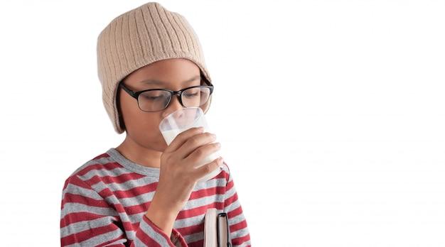 Śliczna azjatycka chłopiec jest ubranym szkła pije zdrowego mleko