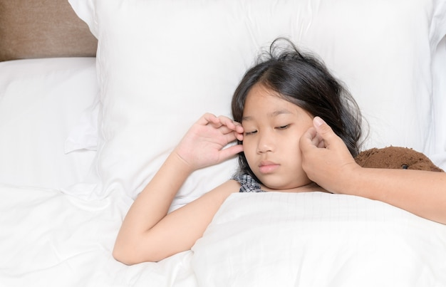 Śliczna azjatycka choroba dziewczyny i ręka matki dotykają jej czoła, aby sprawdzić koncepcję temperatury, opieki zdrowotnej i miłości
