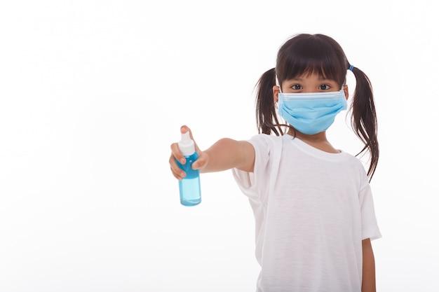 Śliczna azjatycka dziewczyna jest ubranym maskę i trzyma alkoholu gel