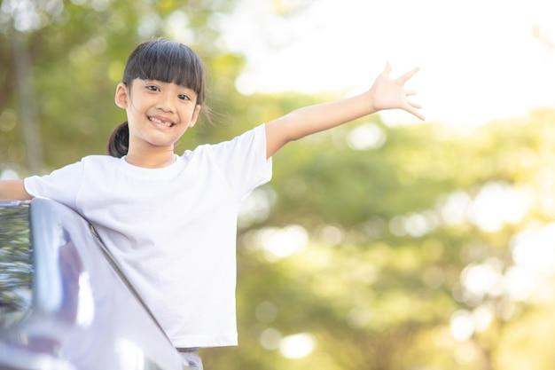 Śliczna azjatycka dziewczynka bawi się podróżując samochodem i patrząc przez okno na wsi?