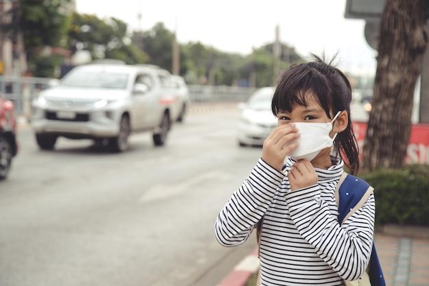 Śliczna azjatycka dziewczynka nosząca maskę ochronną przed zanieczyszczeniem powietrza smogiem z pm 2,5 w mieście