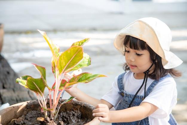 Śliczna azjatycka dziewczynka sadząc drzewo w doniczce z chwilą szczęścia, koncepcją uczenia się, szkołą domową i podstawowymi umiejętnościami życiowymi dla rozwoju dziecka.
