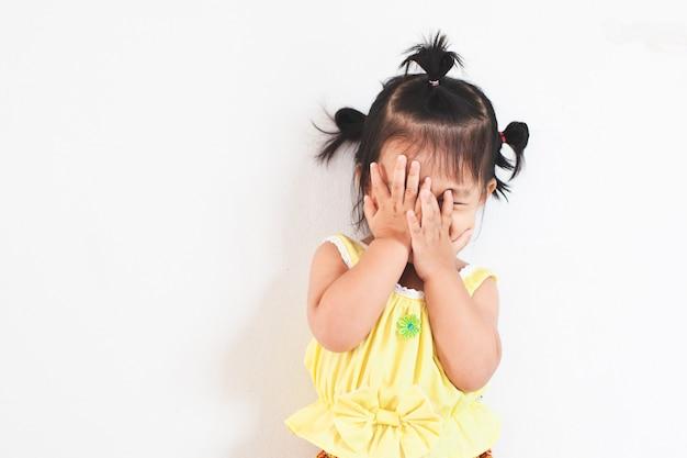 Śliczna azjatycka dziewczynka zamykająca twarz i grająca w chowanego lub chowająca się z zabawą