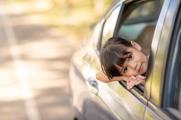 Śliczna azjatycka mała dziewczynka bawi się podróżując samochodem i wygląda przez okno