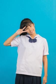 Śliczna azjatycka uczennica pokazuje dwa palca na błękicie.