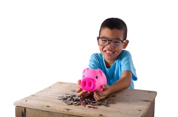 Śliczna azjatykcia chłopiec bawić się z prosiątko bankiem