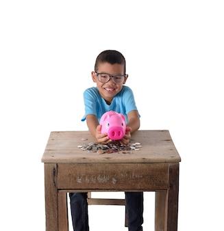 Śliczna azjatykcia chłopiec zabawę z prosiątko bankiem odizolowywającym na białym tle