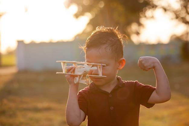Śliczna azjatykcia dziecko chłopiec bawić się z zabawkarskim drewnianym samolotem w parku przy zmierzchu czasem z zabawą
