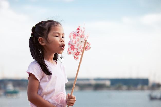 Śliczna azjatykcia dziecko dziewczyna bawić się z zabawkarskim silnikiem wiatrowym w plaży z szczęściem