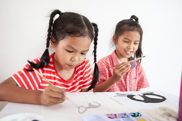 Śliczna azjatykcia dziecko dziewczyna i jej siostra robi pracie domowej szczotkuje wpólnie ich obraz z akwarelą i maluje