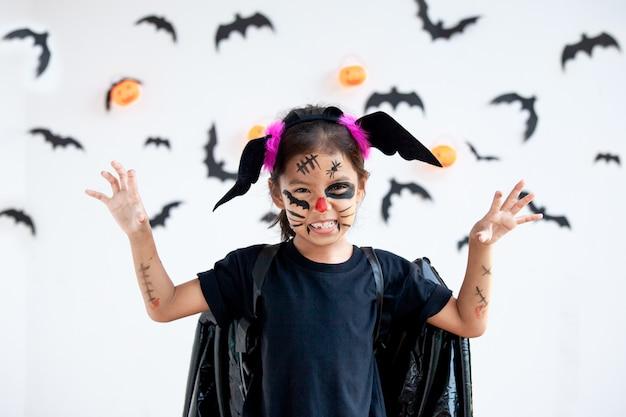 Śliczna azjatykcia dziecko dziewczyna jest ubranym halloween kostiumy i makeup ma zabawę na halloweenowym świętowaniu