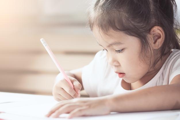 Śliczna azjatykcia dziecko dziewczyna ma zabawę rysować i malować z kredką w rocznika koloru brzmieniu
