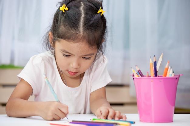 Śliczna azjatykcia dziecko dziewczyna ma zabawę rysować i malować z kredką