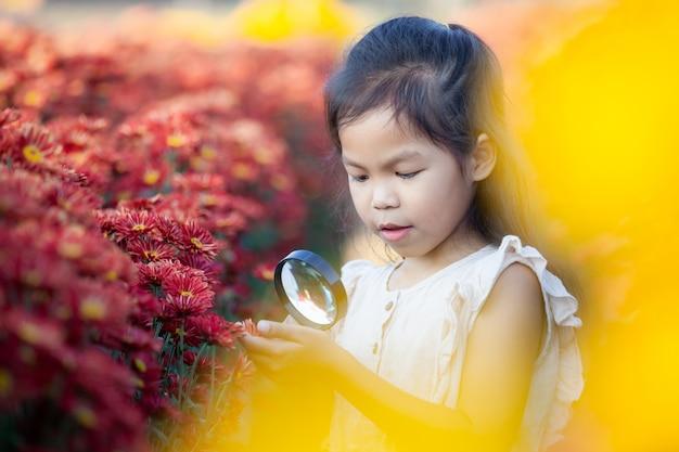 Śliczna azjatykcia dziecko dziewczyna patrzeje pięknego kwiatu przez powiększać - szkło w kwiatu polu