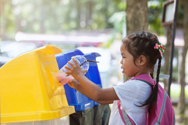 Śliczna azjatykcia dziecko dziewczyna rzuca plastikowego szkło w przetwarzać kosz na śmieci przy jawnym parkiem