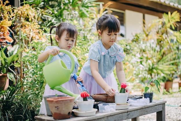 Śliczna azjatykcia dziecko dziewczyna sadzi rośliny w ogródzie lub cutivate