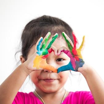 Śliczna azjatykcia dziecko dziewczyna z rękami malować robi kierowemu kształtowi na białym tle