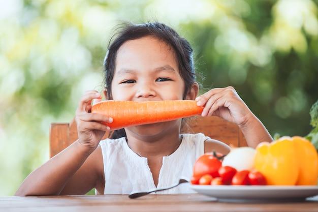 Śliczna azjatykcia dziecko dziewczyny łasowania marchewka i uczenie o warzywach z szczęściem