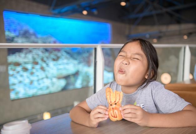 Śliczna azjatykcia dziewczyna cieszy się jeść chleb przy sklepem wielobranżowym