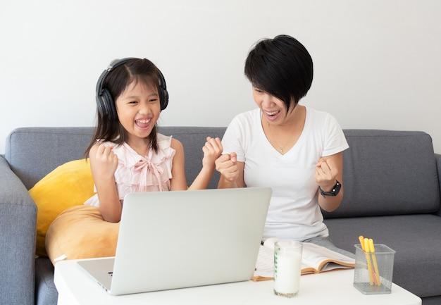 Śliczna azjatykcia dziewczyna i jej nauczyciel używamy notatnika do studiowania lekcji online podczas domowej kwarantanny