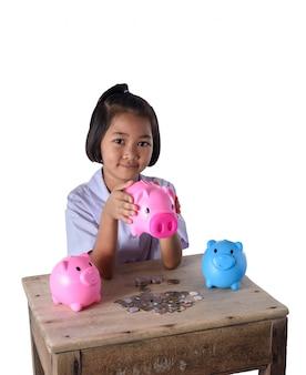 Śliczna azjatykcia dziewczyna zabawę z wiele prosiątko bankiem odizolowywającym na białym tle