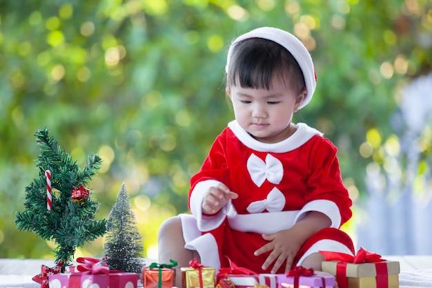 Śliczna azjatykcia dziewczynka jest ubranym santa kostium z pięknymi prezentów pudełkami na bożenarodzeniowym świętowaniu
