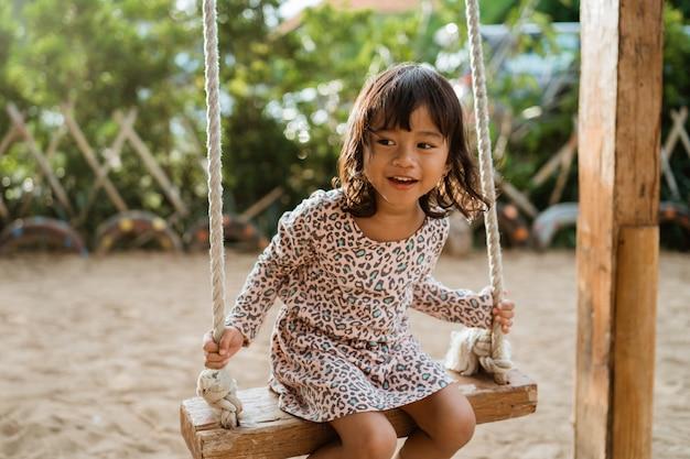 Śliczna azjatykcia mała dziewczynka bawić się huśtawkę w boisku