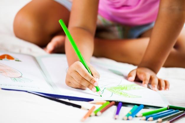 Śliczna azjatykcia mała dziewczynka rysuje z jej kredkami. vintage koloryt. ścieśniać