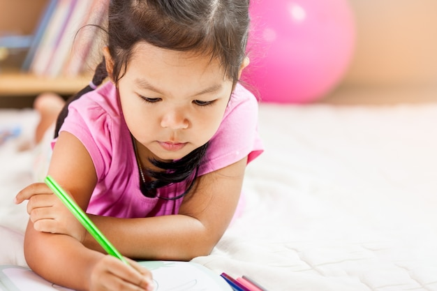 Śliczna azjatykcia mała dziewczynka rysuje z jej kredkami. vintage koloryt