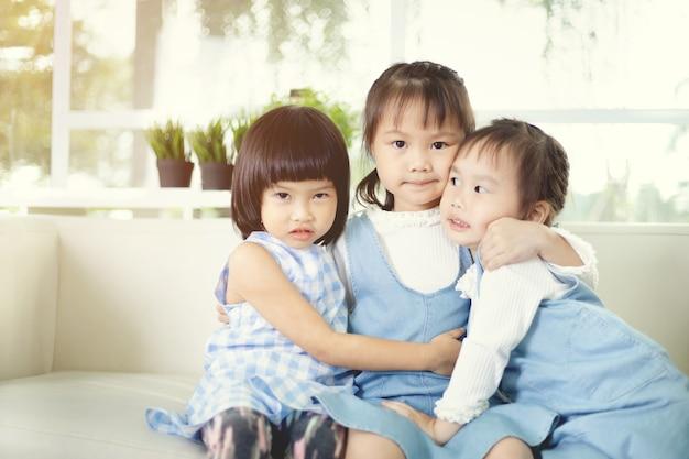 Śliczna azjatykcia mała dziewczynka ściska each inny w domu.