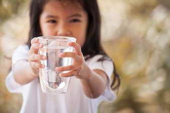 Śliczna azjatykcia mała dziewczynka trzyma szkło świeża woda w rocznika koloru brzmieniu