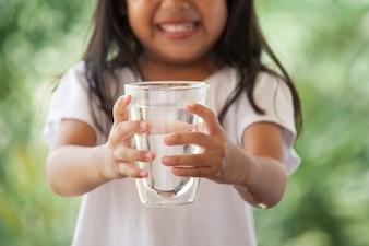 Śliczna azjatykcia mała dziewczynka trzyma szkło świeża woda w zielonym natury tle