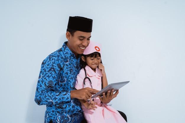 Śliczna azjatykcia mała dziewczynka w lekarka mundurze z jej ojcem