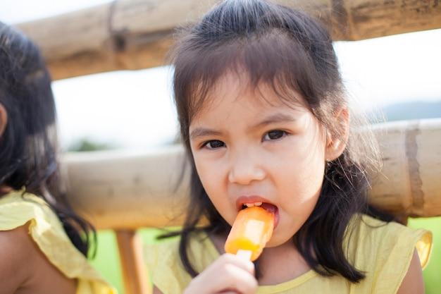 Śliczna azjatykcia małe dziecko dziewczyna je lody w parku