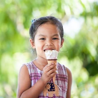 Śliczna azjatykcia małe dziecko dziewczyna je wyśmienicie lody rożek z zabawą i szczęściem