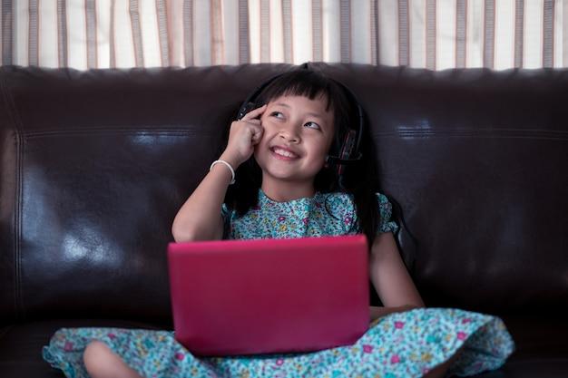 Śliczna azjatykcia małe dziecko dziewczyna myśleć i studiuje online lekcję w domu, socjalny odległość podczas kwarantanny, online edukaci pojęcie