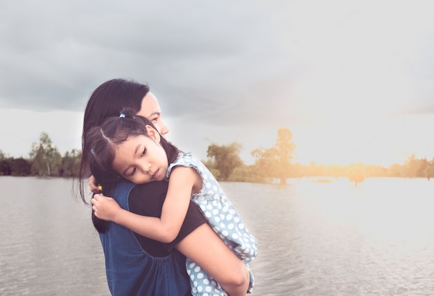 Śliczna azjatykcia małe dziecko dziewczyna odpoczywa na matki ramieniu przy brzeg rzeki w chmurnym dniu