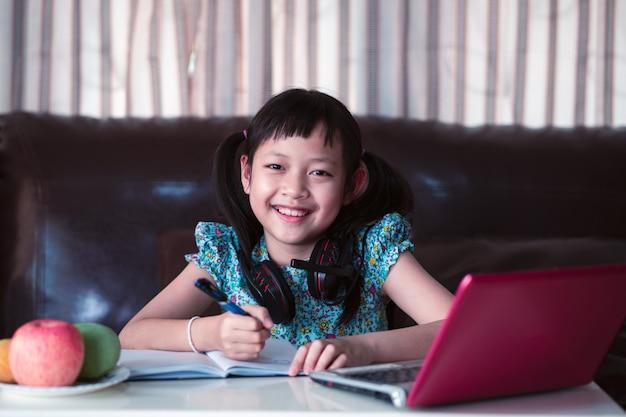 Śliczna azjatykcia małe dziecko dziewczyna studiuje online lekcję w domu, socjalny odległość podczas kwarantanny, online edukaci pojęcie