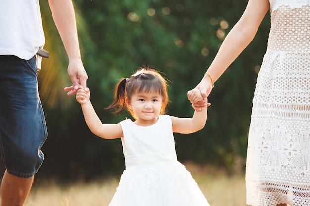 Śliczna azjatykcia małej dziewczynki mienia ręka i odprowadzenie z jej rodzicami w parku