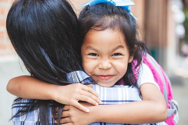 Śliczna azjatykcia uczeń dziewczyna ściska jej matki z szczęściem po plecy od szkoły z plecakiem