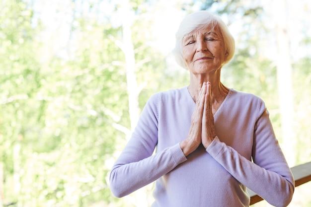 Śliczna babcia w codziennym stroju, trzymająca ręce złożone razem na piersi, relaksując się w letni dzień na wsi