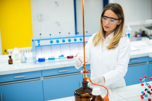 Śliczna badaczka w ochronnej odzieży roboczej stojąca w laboratorium i analizująca kolbę z płynną próbką